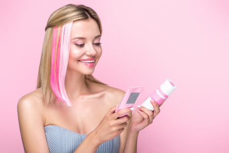 happy young woman with colorful hair strands holding hair treatments isolated on pink