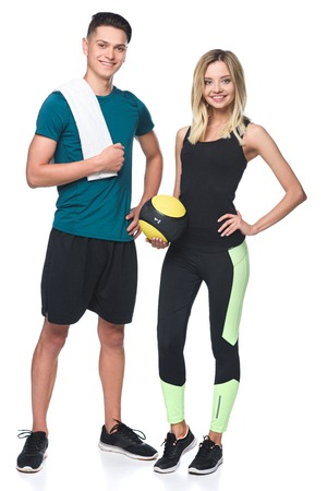 young athletic couple with fitball and towel looking at camera isolated on white