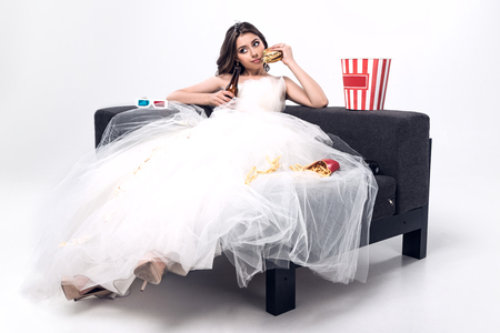 410b92736ae sad young bride in wedding dress sitting on couch with beer and junk food  on white
