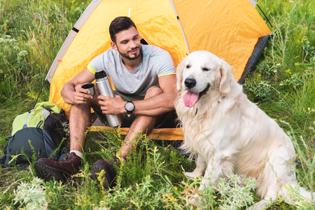 traveler with thermos sitting in tent and looking at dog