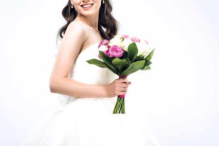 cropped shot of smiling young bride in wedding dress with bouquet isolated on white