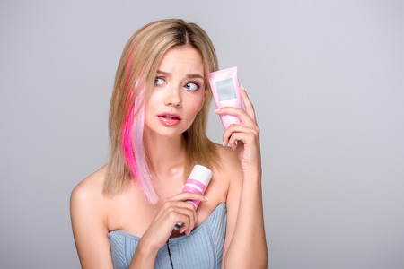 bewildered young woman with colored bob cut holding hair care supplies isolated on grey Stok Fotoğraf