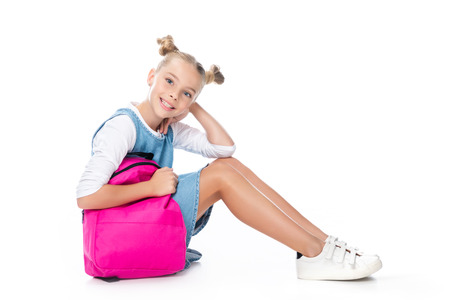 schoolchild sitting with pink backpack and looking at camera isolated on white 스톡 콘텐츠 - 107903827