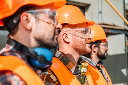 side view of group of equipped builders standing at construction site