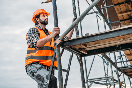 bearded builder climbing on scaffolding at construction site