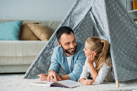 happy father and daughter lying on floor inside of teepee and reading book together at home