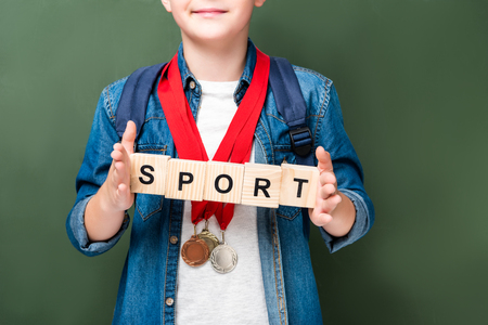 cropped image of schoolboy with medals holding wooden cubes with word sport near blackboard Stock Photo