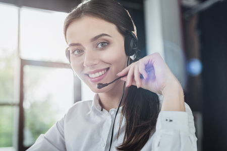 beautiful female call center worker with headphones looking at camera Stok Fotoğraf