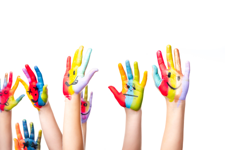 cropped image of schoolchildren showing painted hands with smiley icons isolated on white Foto de archivo
