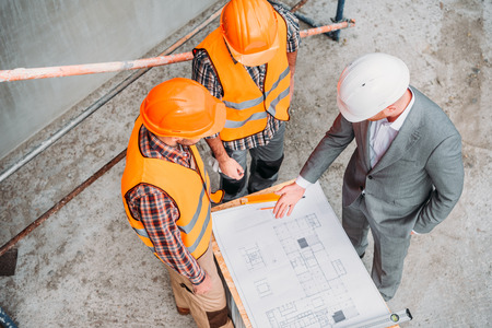 high angle view of builders and architect discussing blueprint at construction site Stockfoto