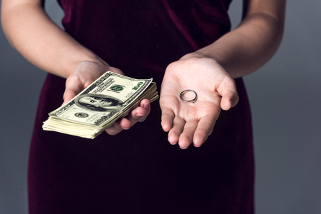 cropped shot of woman holding stack of cash and wedding ring, marriage of convenience concept