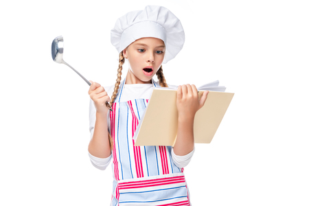shocked schoolchild in costume of chef reading cookbook isolated on white
