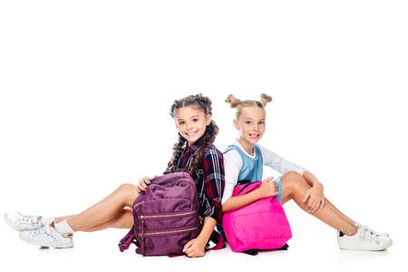 schoolchildren sitting with backpacks and looking at camera isolated on white