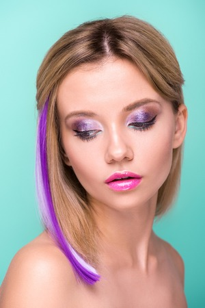 close-up portrait of attractive young woman with stylish makeup and purple hair strand isolated on blue