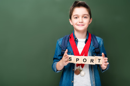 schoolboy with medals holding wooden cubes with word sport near blackboard