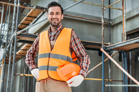 happy builder in reflective vest holding helmet while standing in front of building house and looking at camera