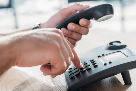 cropped shot of man making dialing stationary phone to make call Stock Photo