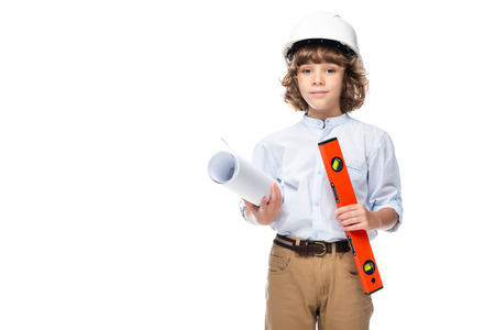 schoolboy in costume of architect and helmet holding blueprints and spirit level isolated on white Stock Photo