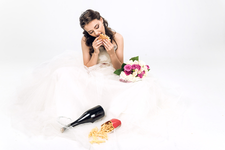 high angle view of young bride in wedding dress eating fast food while sitting on floor on white