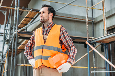 handsome builder in reflective vest holding helmet while standing in front of building house and looking away Imagens