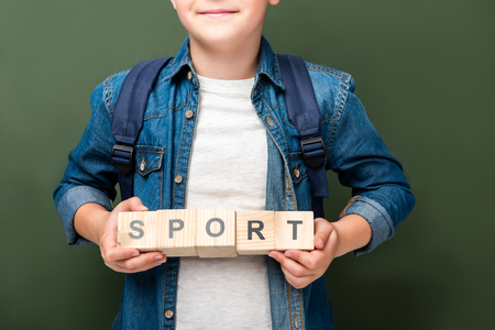 cropped image of schoolboy holding wooden cubes with word sport near blackboard Imagens