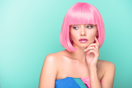 thoughtful young woman with pink bob cut looking away isolated on turquoise Stock Photo