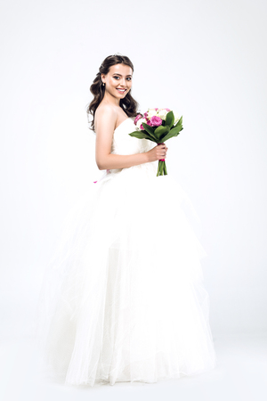 beautiful young bride in wedding dress with bouquet and looking at camera on white