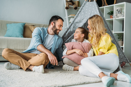 happy young family sitting on floor with teepee Reklamní fotografie