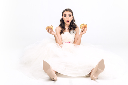 shocked young bride in wedding dress sitting on floor with burgers in hands on white