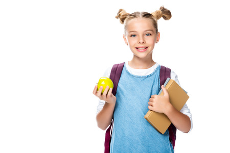 smiling schoolchild holding apple and books isolated on white
