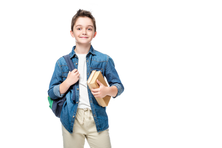 schoolboy holding backpack and books isolated on white Imagens