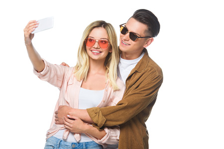 happy young couple taking selfie with smartphone isolated on white