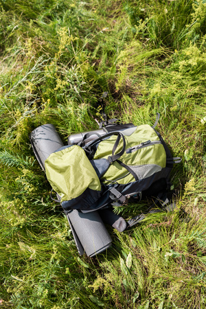top view of backpack with tourist mat and thermos on green grass Banco de Imagens