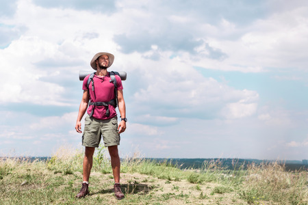 handsome hiker with backpack standing on summer meadow with cloudy sky