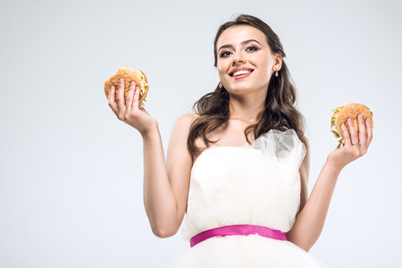 bottom view of young bride in wedding dress holding burgers in hands isolated on white Stock fotó