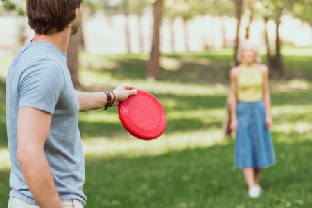 young couple playing frisbee with red frisbee disk in park