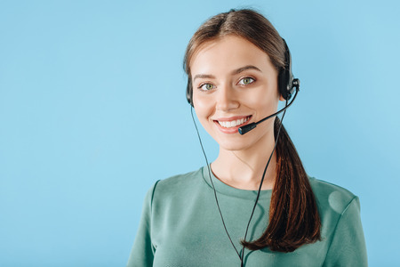 attractive smiling female call center worker looking at camera isolated on blue
