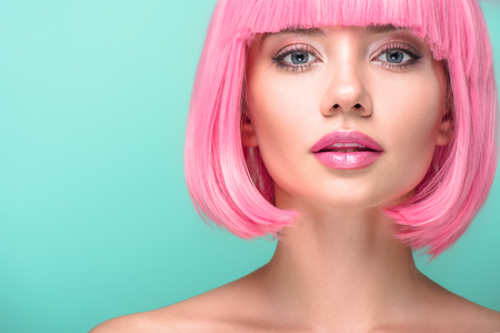 close-up portrait of young woman with pink bob cut looking at camera isolated on turquoise