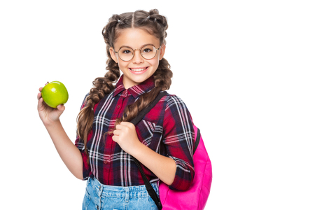 smiling schoolchild with backpack holding apple isolated on white