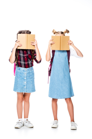schoolchildren covering faces with books isolated on white Stock fotó