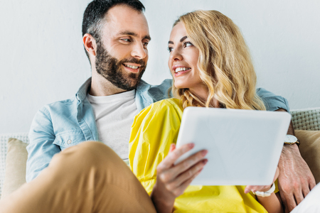 happy couple using tablet together while sitting on couch at home 版權商用圖片