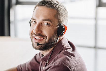 handsome smiling call center worker in headphones with microphone looking at camera