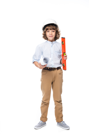 schoolboy in costume of architect and helmet holding blueprints and bubble level isolated on white Stock Photo