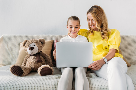 mother and daughter using laptop together while sitting on couch together at home Stock Photo