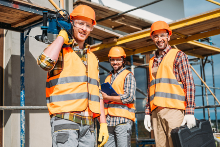 group of smiling builders with building equipment standing at construction site and looking at camera