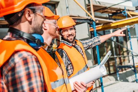 Nahaufnahmeaufnahme einer Gruppe von ausgerüsteten Bauherren, die weg auf Baustelle schauen Standard-Bild