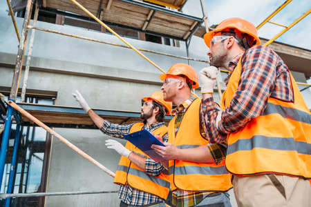 group of builders in hard hats and reflective vests pointing at building house