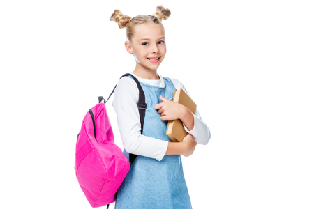 smiling schoolchild with pink backpack holding books and looking at camera isolated on white