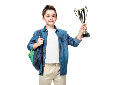 adorable schoolboy with backpack holding winner cup isolated on white Banco de Imagens