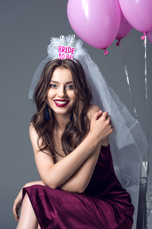 happy future bride in veil for bachelorette party sitting on chair with tied pink balloons isolated on grey Imagens